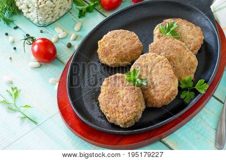 Domestic Meat Cutlet With White Beans And Fresh Herbs. Cast-iron Frying Pan Full Of Delicious Fried