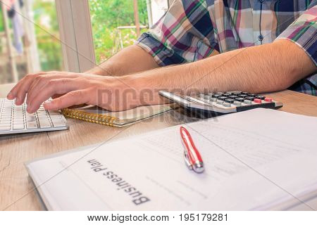 Close up view of bookkeeper or financial inspector hands making report calculating or checking balance. Business plan calculator on the table - color / Old Polaroid