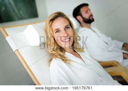 Beautiful woman in bathrobe with handsome man relaxing in spa