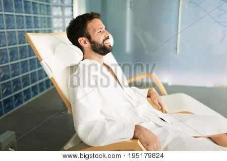 Handsome man relaxing in chair at spa center wearing bathrobe