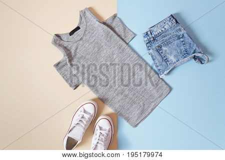 Fashionable Concept. Women's Urban Style. Gray T-shirt, White Sneakers And Jeans Shorts On A Soft Bl
