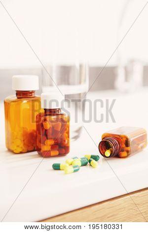 Spilt bottle of pills on counter in bathroom close up