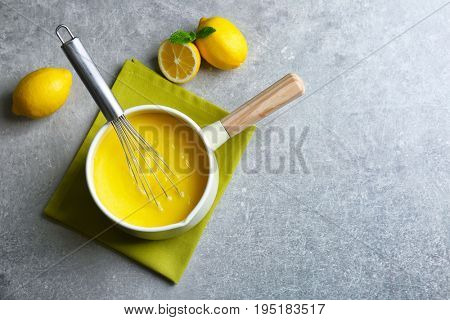 Sauce pan with delicious lemon curd and whisk on table