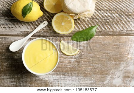 Composition with delicious lemon curd on wooden table