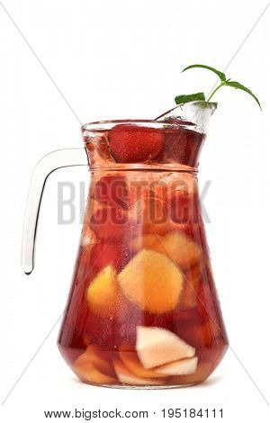 a glass pitcher with typical spanish sangria with some pieces of fresh fruit on a white background