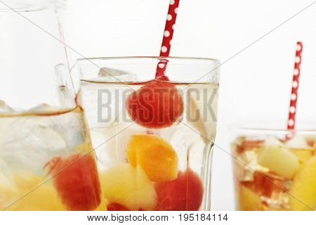 closeup of a pitcher and some glasses with refreshing spanish sangria blanca, white sangria, with pieces of fresh fruit, on a white background