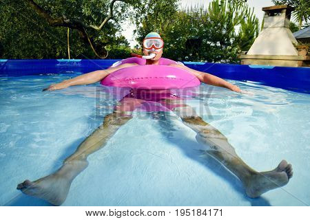 young caucasian man wearing a diving mask, a snorkel, a bath cap and a swim ring, swimming in a portable swimming pool placed in the backyard