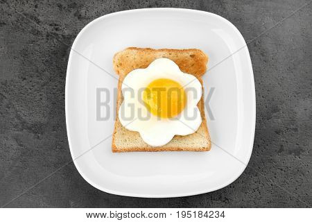 Plate with delicious sunny side up egg and toast on dark background