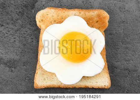 Delicious sunny side up egg with bread on dark background