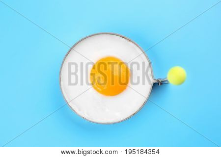 Fried sunny side up egg in round mold on color background