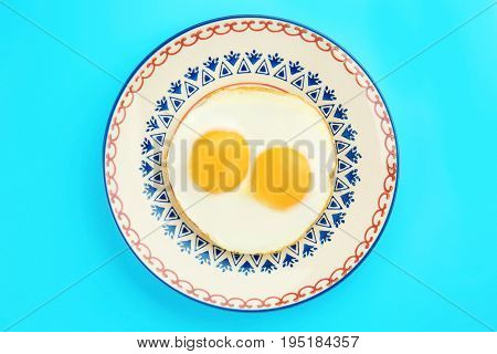 Plate with delicious sunny side up eggs on color background
