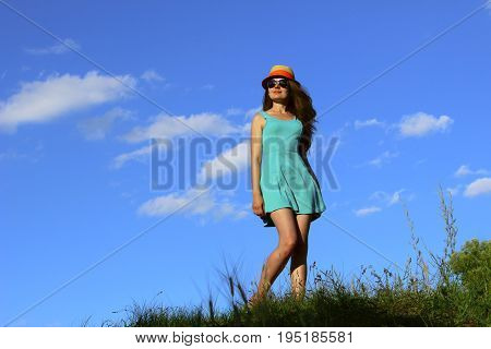 Beautiful young woman wearing sunglasses and a summer straw hat over blue sky background. Full length side view portrait of trendy young Caucasian woman walking outdoors.