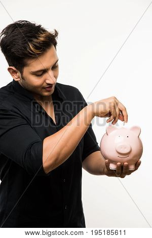 India and finance concept - Handsome Indian man or boy holding pink piggy bank, with different expressions holding indian currency notes of 2000 and 500 or rupee coins, standing over white background