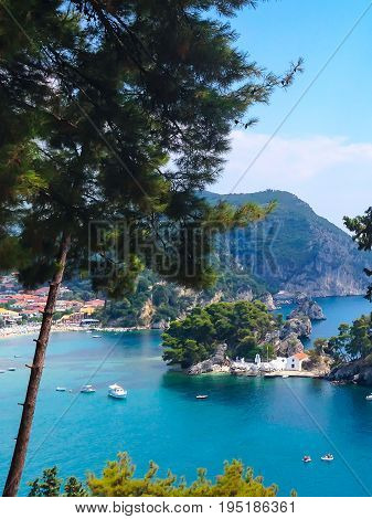Summer vacation background with turquoise sea water bay, boats and pine trees in Parga, Greece