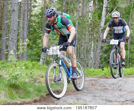 STOCKHOLM SWEDEN - JUNE 11 2017: Group of male mountain bike cyclists in the forest at Lida Loop Mountain bike Race. June 11 2017 in Stockholm Sweden