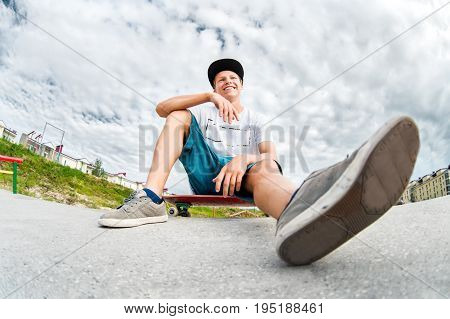A young laughing skater in a cap and shorts is resting sitting on his skateboard in a skatepark