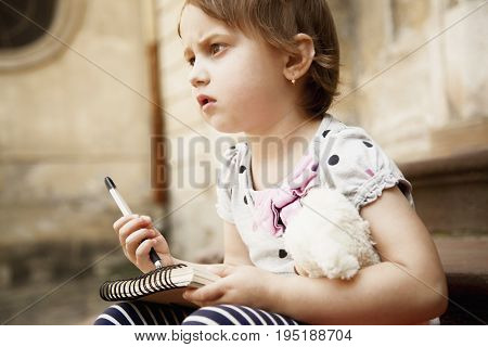 Little business child girl writing in notebook and planning her workday. Humorous picture. Time management business job offer analytics research concept.