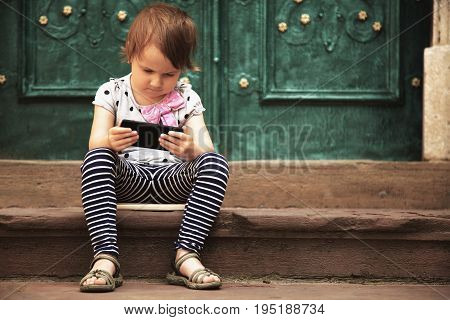 Little beautiful child girl using smartphone as symbol pf work or study. Connect to the Internet with smartphone. (Development education technology concept)