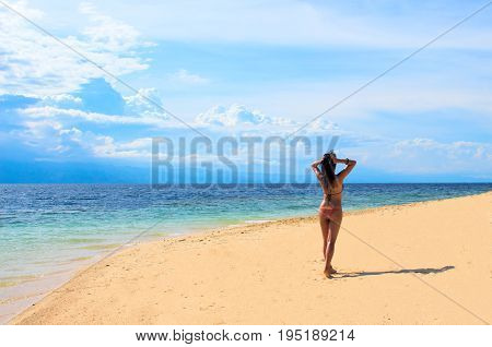 Summer beach photo. Woman on vacation. Beautiful girl on beach. Young woman in bikini under sunlight. Tropical island paradise holiday travel. White sand beach and blue seawater. Perfect beach view