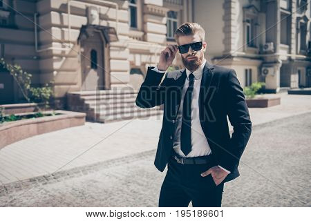 Portrait Of A Harsh Agent Outdoors In The City. He Looks Stunning And Severe, Wearing Suit And Sungl