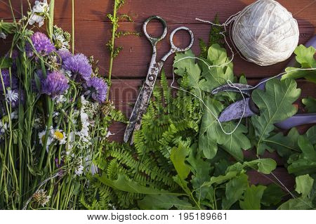 Top view on wooden table with meadow grasses, fern, oak leaves and tools for wreath making.