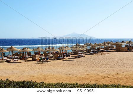 SHARM EL SHEIKH EGYPT - NOVEMBER 29: The tourists are on beach at popular hotel on November 29 2013 in Sharm el Sheikh Egypt. Up to 12 million tourists have visited Egypt in year 2013.