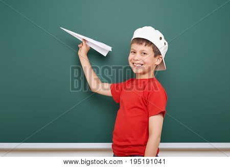 Schoolboy with paper plane play near a blackboard, empty space, education concept