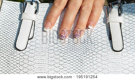 Hands with a manicure hold a white handbag