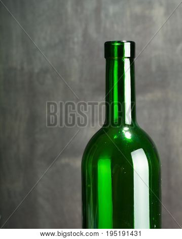 High wine glass made from green glass. No content. Side view. Low key.