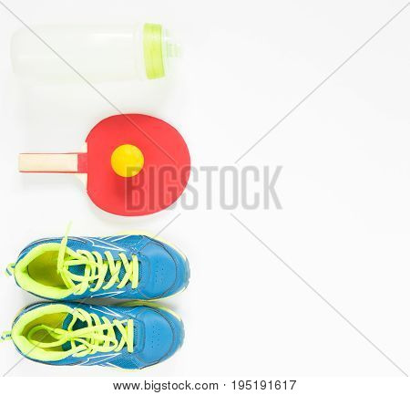 Sport background. Red ping-pong racket and orange ball . Flat lay blue treiners water bottle. Flat lay top view.
