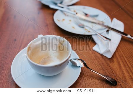 A dirty plate and an empty cup of coffee. Empty dishes after eating on a wooden table in a cafe.