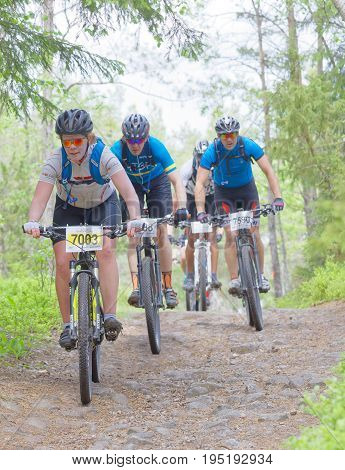 STOCKHOLM SWEDEN - JUNE 11 2017: Group of mountain bike cyclists in the forest cycling downhill at Lida Loop Mountain bike Race. June 11 2017 in Stockholm Sweden