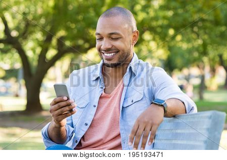 Young african man sitting at park and using smart phone. Happy smiling guy reading a message on cellphone while sitting on a bench in a park. Black man surfing net with smartphone.