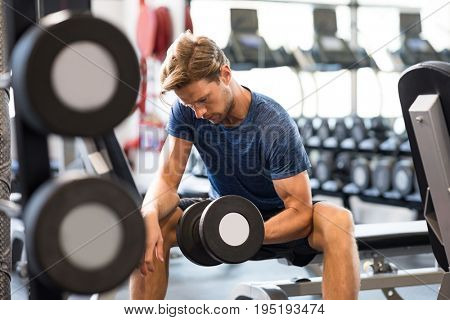 Young handsome man training at a fitness center. Fit guy lifting dumbbell at gym. Portrait of a young muscular man exercising with dumbbells in the gym.