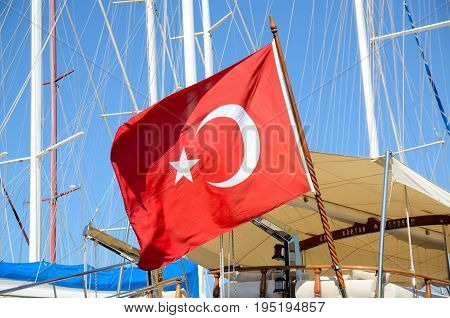 Bodrum port Turkey. Big Turkish flag on ship behind masts and blue sky.