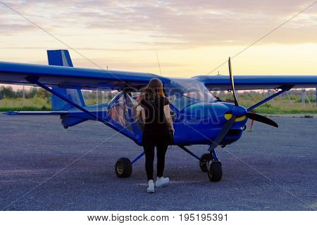 Young girl goes to her plane against the background of the evening sky