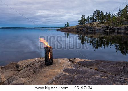 Evening landscape of big lake with stone islands. In the foreground on a stone block, a