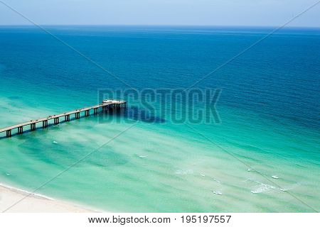 Pier jutting out from beach to ocean under clear blue skies.