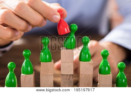 Businessman Replacing The Green Figure With Red Figure On Top Of The Wooden Blocks