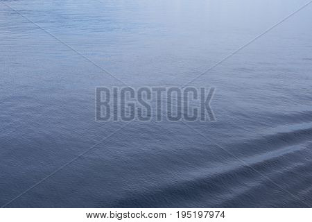 Sea water closeup with rippled surface and blue depth. Oceanic cruise liner trail in clean blue water. Seaside background. Aquatic backdrop. Ocean surface. Seawater top view. Marine ship travel banner