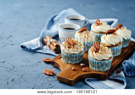 Carrot cinnamon cupcakes with pecan on a stone background