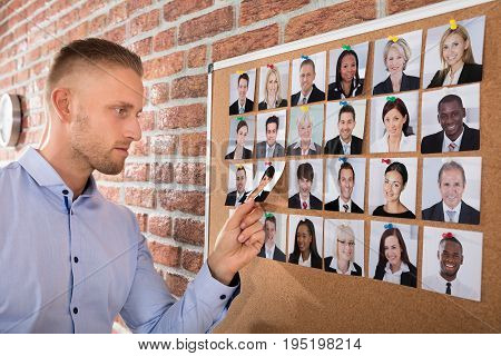 Businessman Selecting Candidates Photo Attached On Corkboard In Office