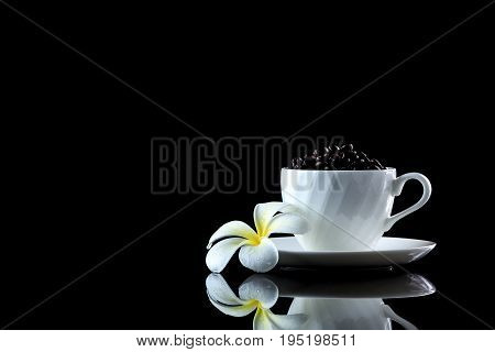 Cup With Coffee Beans And Frangipani On A Black Reflective Background