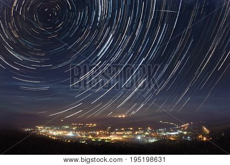 A picture of star tracks over mountain town