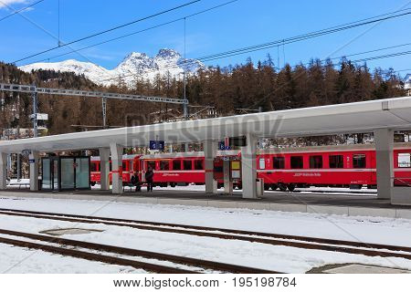 St. Moritz, Switzerland - 3 March, 2017: a platform of the St. Moritz railway station, a passenger train of the Rhatische Bahn company at it, mountains in the background. St. Moritz is an Alpine resort in the Swiss canton of Graubunden.