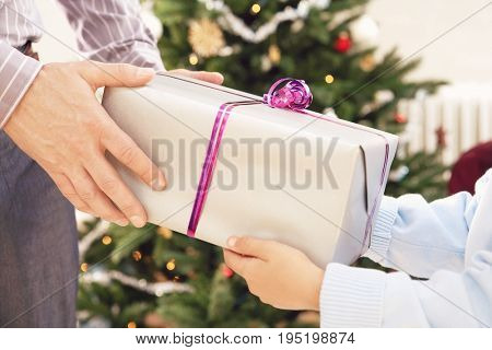 Closeup of father giving Christmas present to son