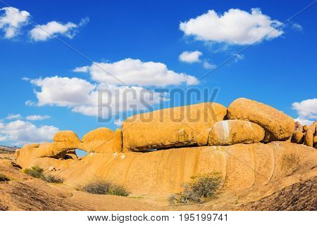 Stone arch Spitzkoppe, Namibia. The concept of extreme and ecological tourism. Natural array of bald granite outcrops among the Namib Desert