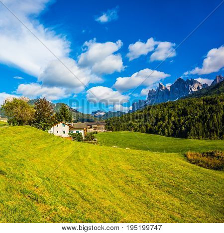The valley is surrounded by a dentate wall of dolomite rocks. Charming chalet on a green grassy slope. Warm autumn in the Dolomites. The concept of ecological tourism