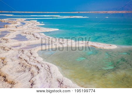 Hot summer day at the seaside resort. Walk on the Dead Sea, Israel. The evaporated salt has developed into fantastic patterns. The concept of medical and ecological tourism