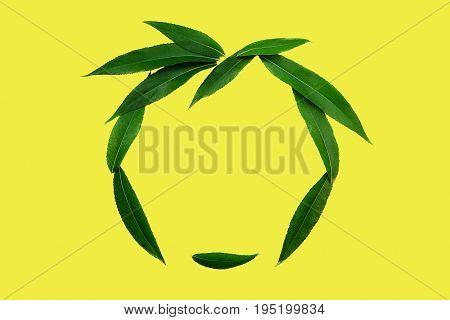 The Face Of Green Leaves - аbstract Summer Symbol And Good Mood On A Yellow Background. Minimal Styl